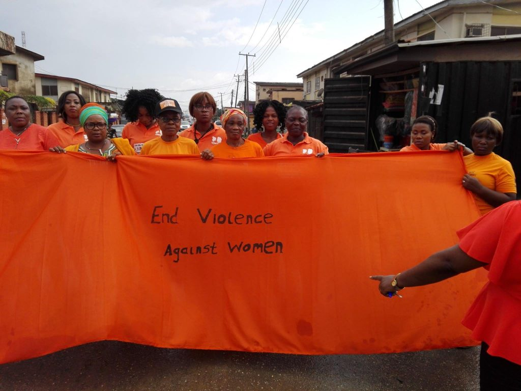 AmplifyChange grantee, GIWYN at a march for ending violence against women in Nigeria. They are holding up an orange banner with the text 'End violence against women'.